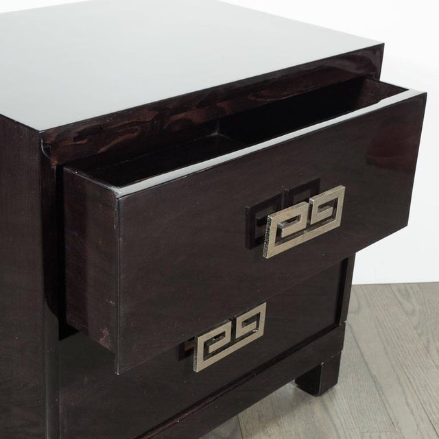 A pair of Mid-Century end tables or nightstands in hand-rubbed ebonized walnut. Two drawers in each feature a polished...
