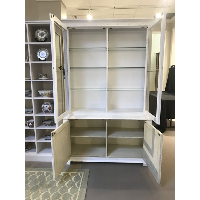 This is a white Milling Road for Baker china / display cabinet with solid wood lower cabinet doors, metal chicken wire...