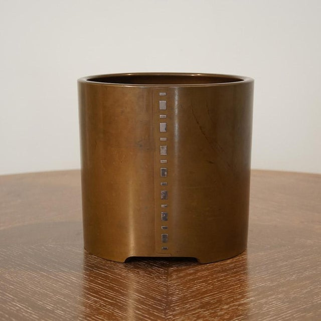 This is a bronze and nickel jardiniere. This Japanese bronze jardiniere has nickel inlays with pronounced seam detail.