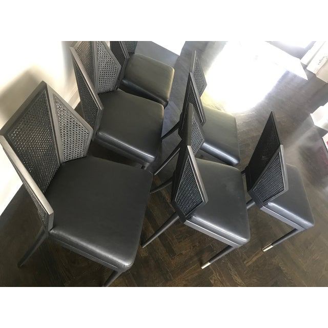 Set of (6) Cane Side Chairs. Finished in blackened walnut with black caning, black leather upholstery, and bronze...