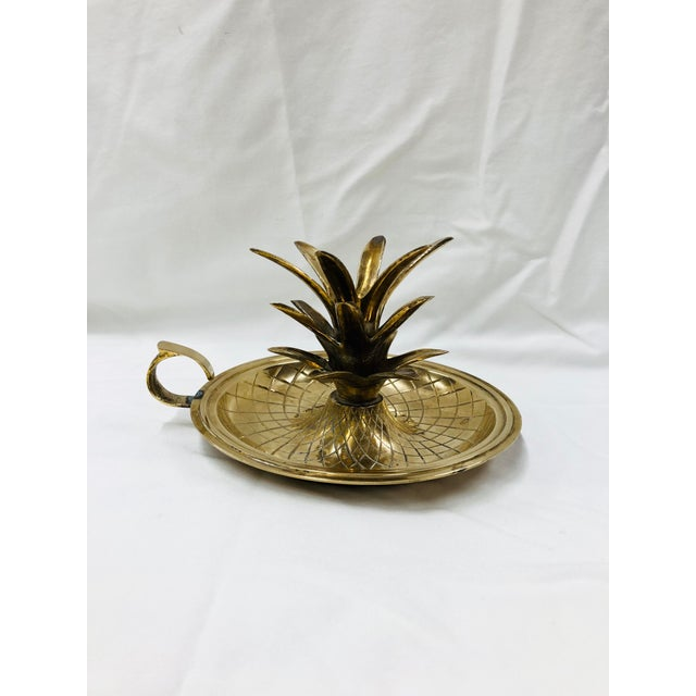 1970s brass pineapple candle holder has finger loop and geometric pattern in a convex stand.