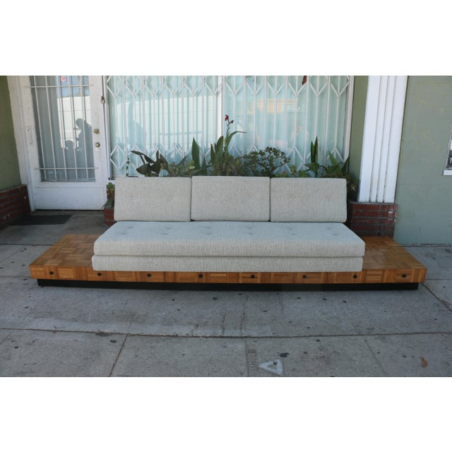 Amazing patched burlwood platform base sofa. The base has been refinished and the sofa has been reupholstered. No damages...