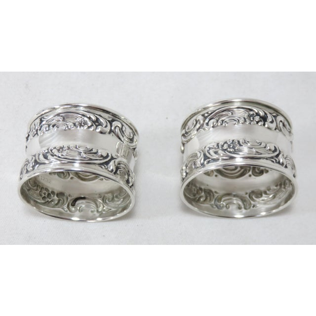 A very pretty matched pair of antique American sterling silver napkin rings. They are repousse decorated in a classic...