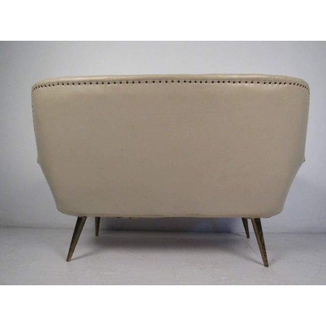 Stylish, sculptural loveseat in warm tan vinyl with brass tack accents and tapered legs. Please confirm item location (NY...