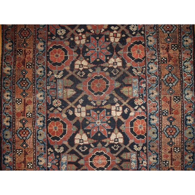 Antique Persian Hamadan runner in good original condition. This rug has black field color and camel hair brown border....