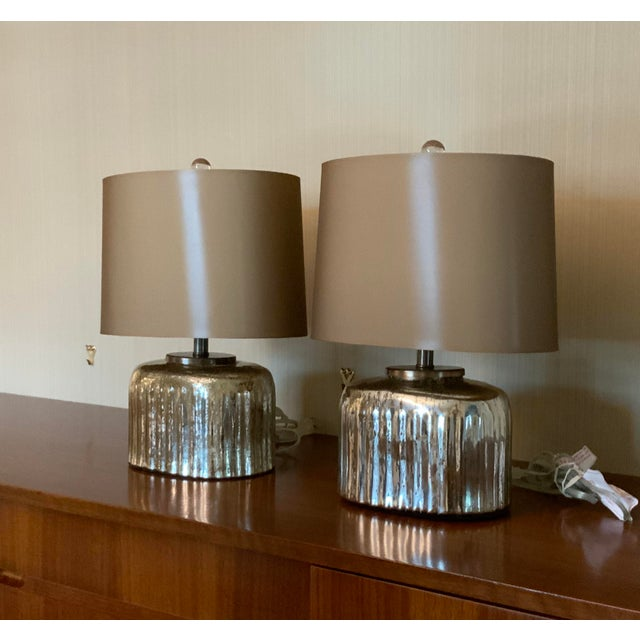 Ribbed mercury glass lamp with fabric shade and clear glass finial.