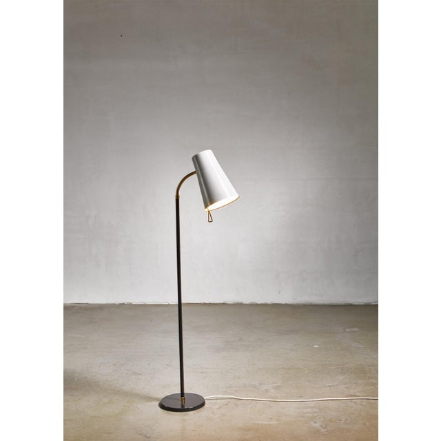 A model 2067 mid-century floor lamp by Yki Nummi for Orno. The adjustable off-white metal hood with a brass goose neck and...