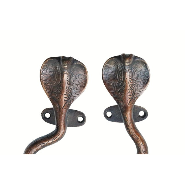 A pair of antiqued dark brass cobra door handles or cabinet pulls. Hollywood Regency in style, with intricate carving...