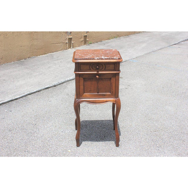 French Louis XV solid walnut night stand or side table marble top circa 1900s. The table is in solid walnut with marble...