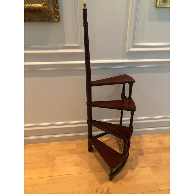 An elegant piece of furniture. English design, mahogany finish spiral library steps. Turned hand support with column...