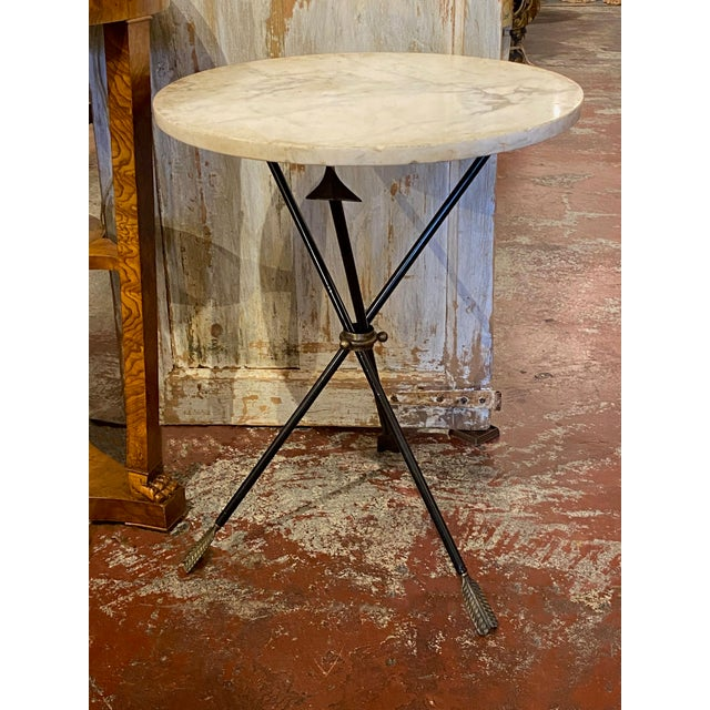 Early 20th century French Carrara marble and iron triad base table. Triad base with arrow tips and feathers in bronze....
