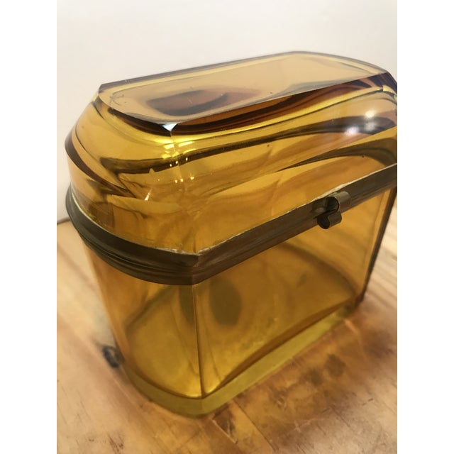 19th Century French amber glass hinged box with gilded brass mounts. There's a hinge in the back and a small clasp at the...