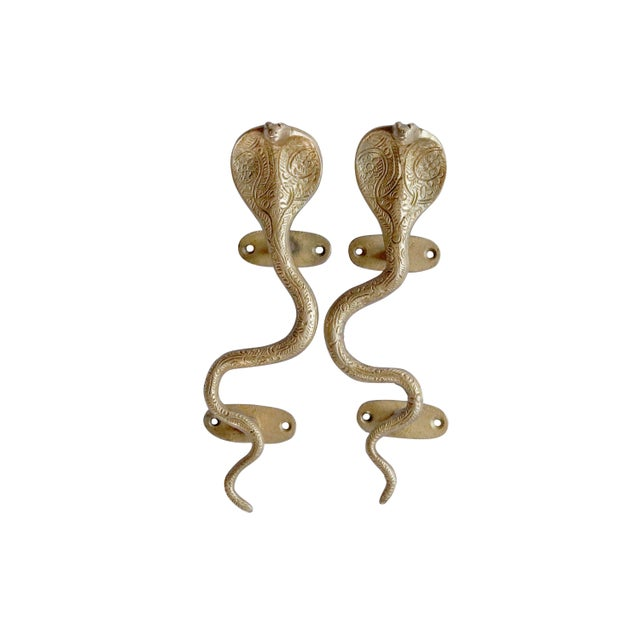 A pair of gold brass cobra door handles or cabinet pulls. Hollywood Regency in style, with intricate carving throughout....