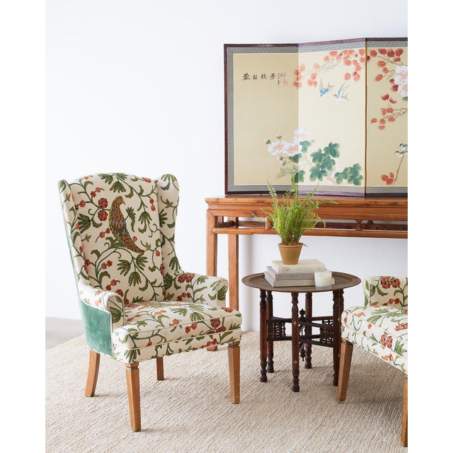 Stunning pair of English style wing chairs or wingback chairs featuring an upholstered crewel work frame. The crewel work...