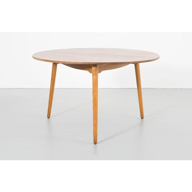 A dining table designed by Hans Wegner for Fritz Hansen in Denmark, c 1950s. Oak and teak. Original labels intact.