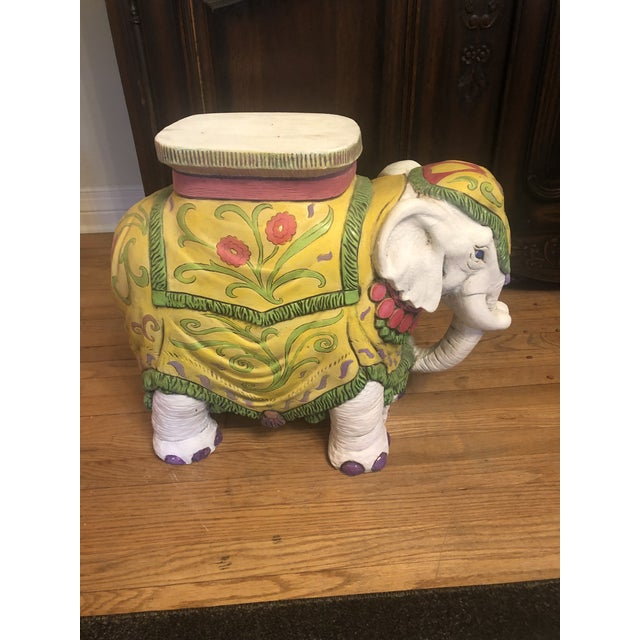 Super cute garden elephant table/seat. It has vibrant colors of yellow, green, and pink.