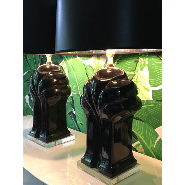 Pair of large sculptural black table lamps in an iconic art deco form. The ceramic body sits on a Lucite plinth base. Each...
