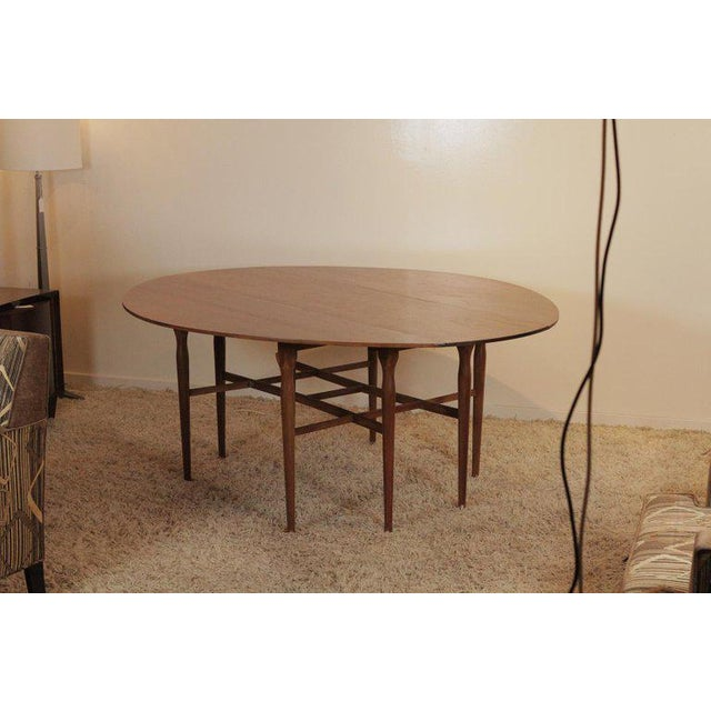 A classic sleek walnut drop-leaf table with two drop leaves. Measures: The table with leaves down, 72 long, 19.5 deep...
