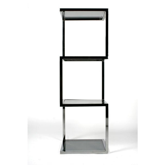 A slick etagere comprising an asymmetrical polished chrome frame of three stacked cubes with four smoked glass inset...