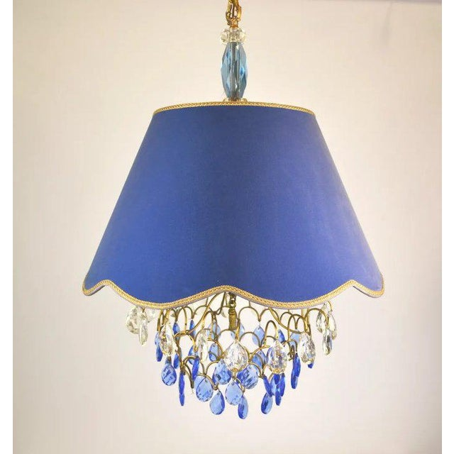 A charming vintage velvet like covered shade pendant with blue and clear crystal chandelier hanging below. The shade has...