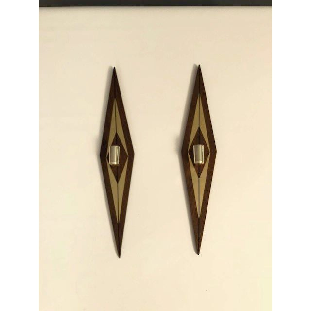 Beautiful pair of mid-century candle wall sconces. Constructed of walnut and brass. Made in the 1970s.