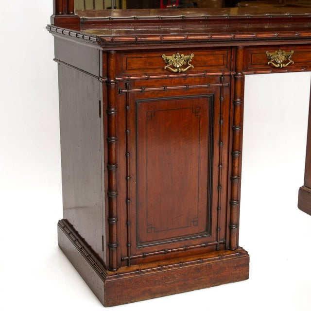 A fine English pedestal sideboard with mirror back and bamboo moldings. The sideboard is made of mahogany wood. With ebony...