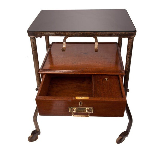 From a decommissioned ship, a teak medial trolley with smoked black glass top, front drawer and brass drawer pull and...
