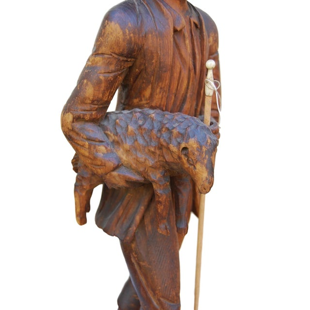 Lovely carving of a shepherd and a lamb. The patina on this piece is outstanding. There is restoration to the nose of the...