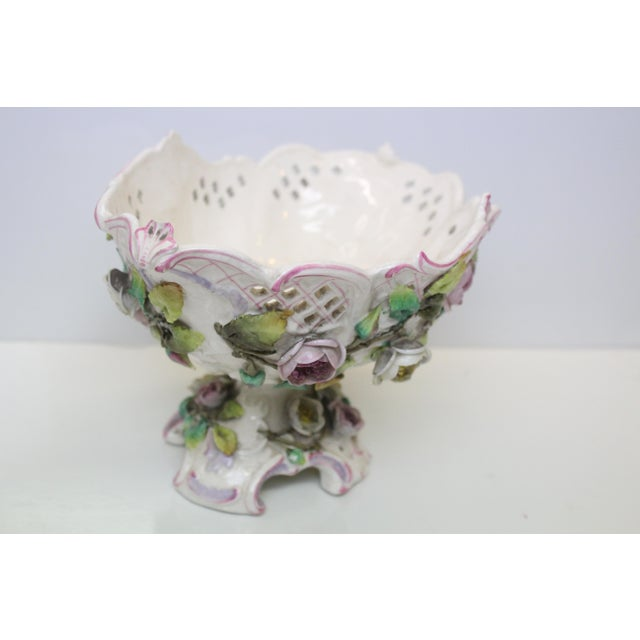 White porcelain footed decorative art nouveau bowl with pink and green floral accents. Delicately punched and formed.