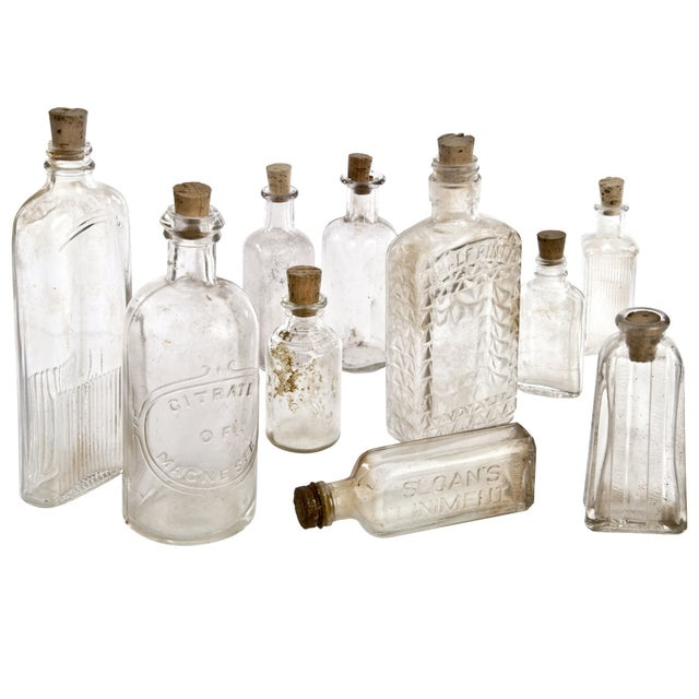 Collection of ten vintage clear glass bottles. Great for display on a shelf or in a windowsill. Assorted flavoring,...