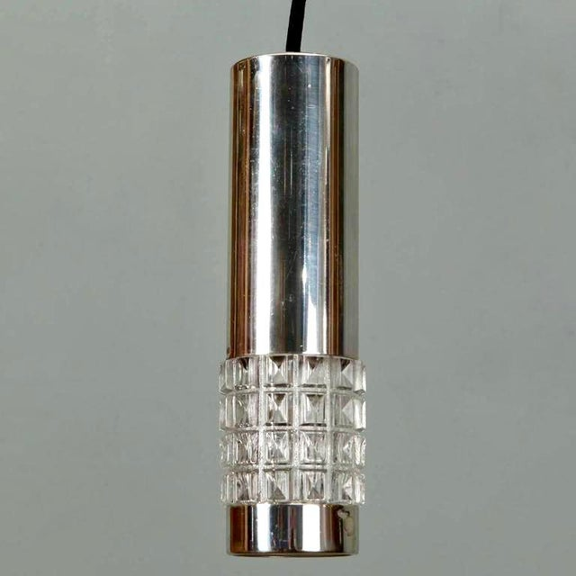 Circa 1970s German chrome pendant light in cylinder form and embellished with wide band of chunky, clear molded glass....