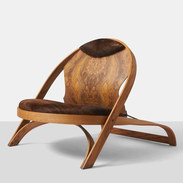 A limited edition chair by Richard Artschwager in oak with cowhide seat and headrest and a painted steel support on the...