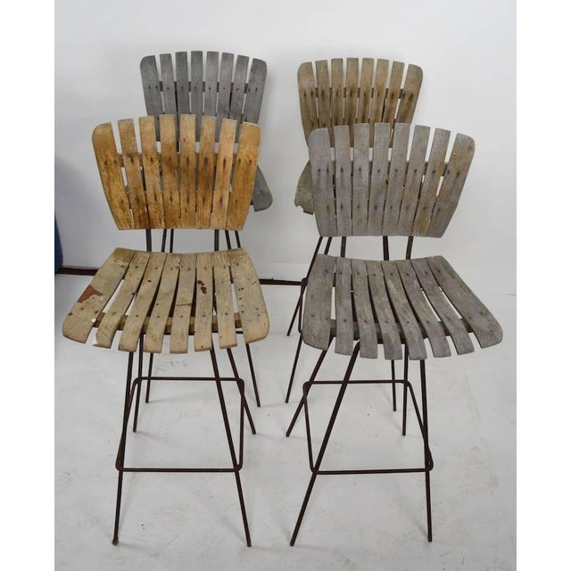 Four swivel stools designed by Arthur Umanoff, in weathered finish. These stools are on squared iron bases (show rust),...