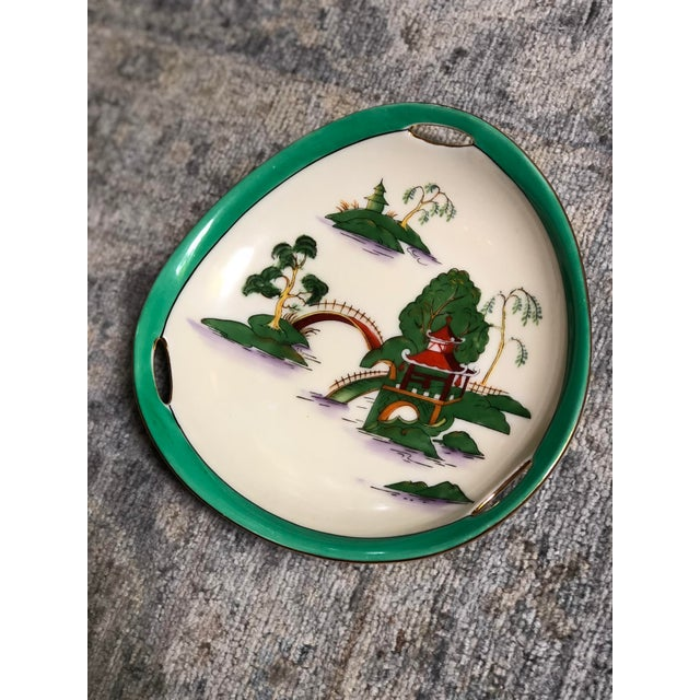Midcentury pair of triangular hand painted ceramic plates with a simple chinoiserie decoration, jade green outer rim, and...