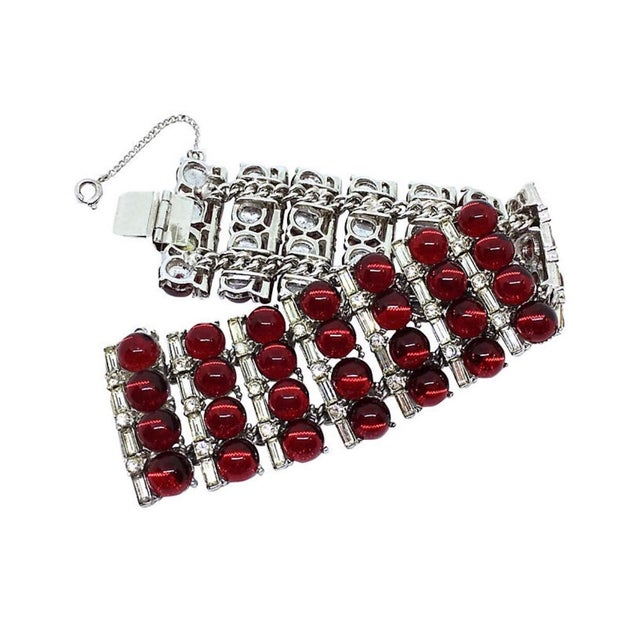 Circa 1960s wide, bright silver tone metal bracelet, set with 8mm round, red glass cabochons and embellished with clear...