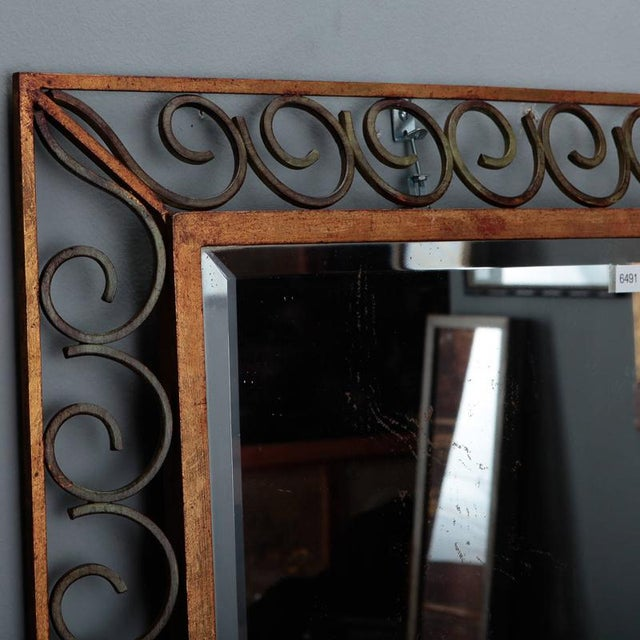 Circa 1930s French rectangular beveled edge mirror with open work scroll frame in gilded and green painted iron. Dealer...
