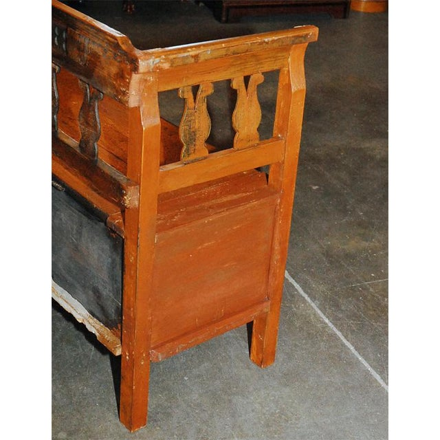 Very large bench, possibly German, in pine with painted elements, circa 1890. The bench has two lids that lift to expose...
