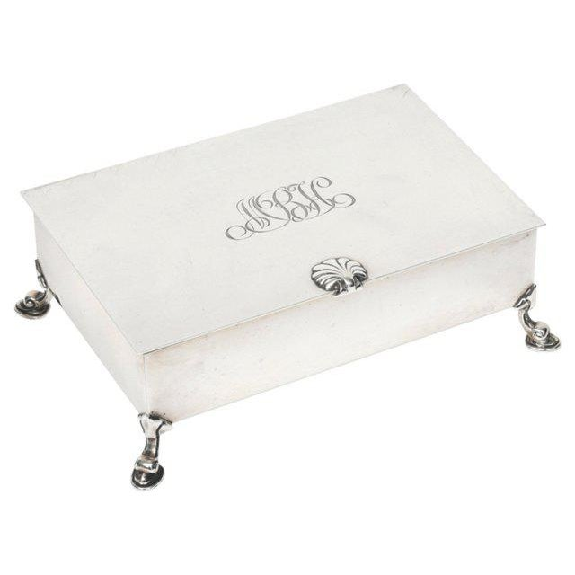 Tiffany & Co. rectangular sterling silver cigarette box rests on four inverted cabriole feet. Top of the box features a...