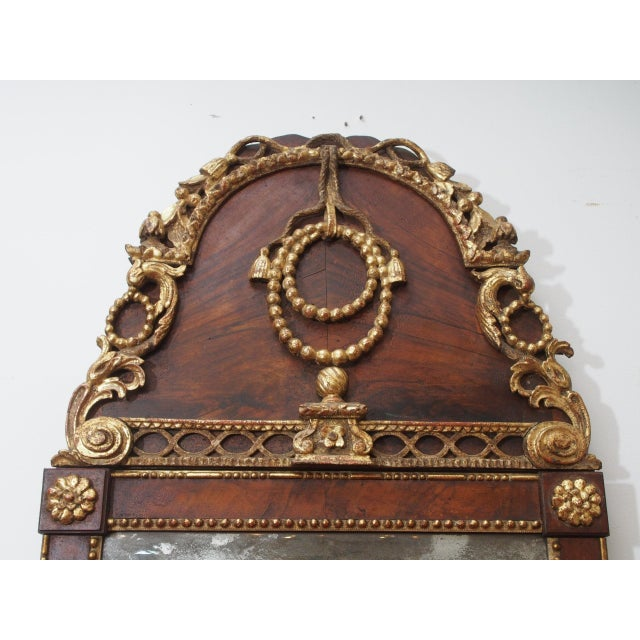 A stunning 18th century mahogany and gilt mirror, the frame with rosettes and beaded molding and over fluted, tapered...