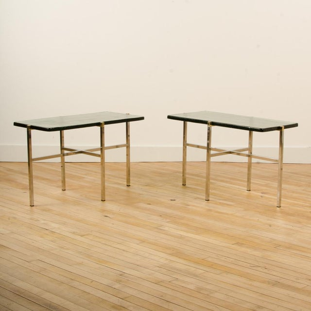 A pair of Italian Mid-Century end tables with thick smoky and textured glass tops resting on chrome and brass legs....
