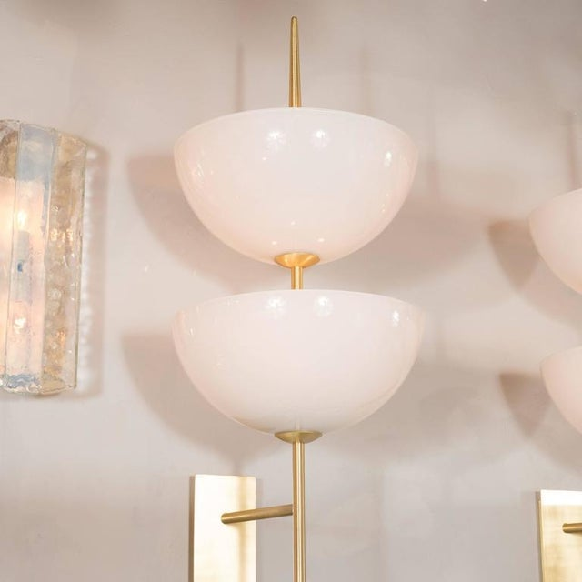 A pair of reverse-dome trophy sconces in milk glass and polished brass. Rectangular back plates support a brass spear-...