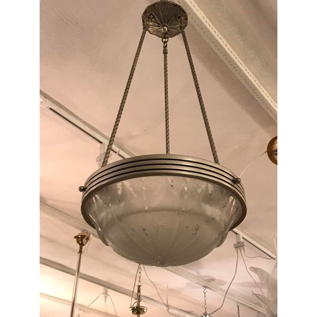 French Art Deco geometric chandelier signed by Muller Frères Luneville. Having a glass shade with geometric and star motif...