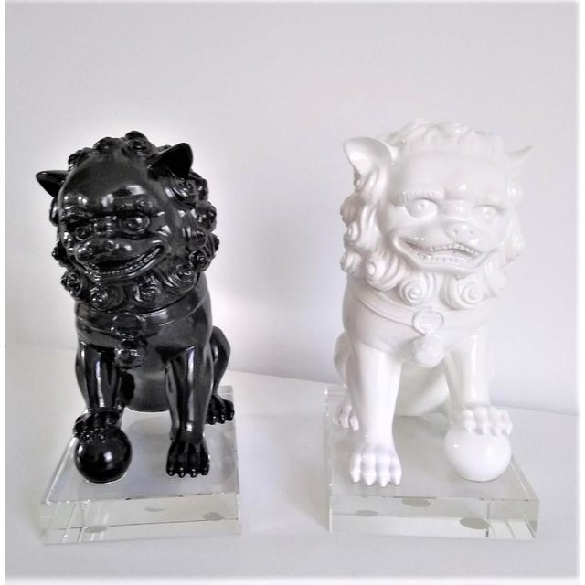 Not you typical Foo Dog sculptures. Striking pair of vintage ceramic Foo (Fu) dog sculptures are painted white and black...