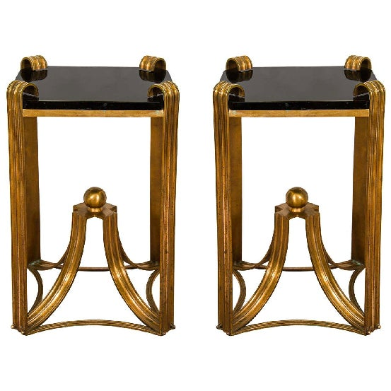 A vintage pair of Art Deco moderne side tables, circa 1930s with curved bronze design and center bronze ball. The thick...