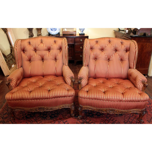 Pair of bergere chairs of broad proportions; wing chair form. French, Louis XV style, c. 1900. Robust leaf carved aprons &...