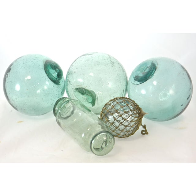 Set of five blue green blown glass Japanese fishing net floats. Some bubbles, straw marks and pontils typical of blown...