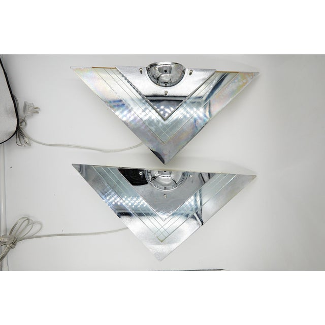 Fabulous pair of 20th century Art Deco mirrored wall sconces of glass and chrome. The V-shaped floating sconces have...