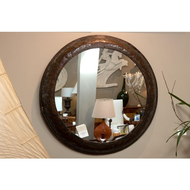 A very large round metal industrial architectural element mounted as a mirror, English circa 1900; dark and richly-aged...
