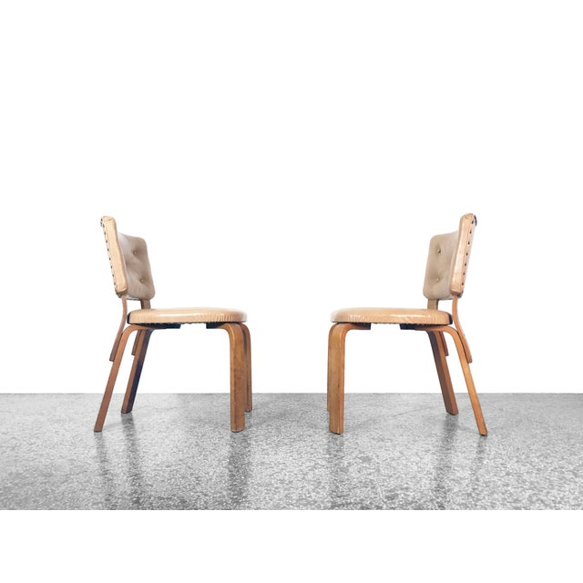 A pair of rare Model 62 upholstered chairs designed by Alvar Aalto, Finland 1940s. Bent birchwood frames with tan vinyl...