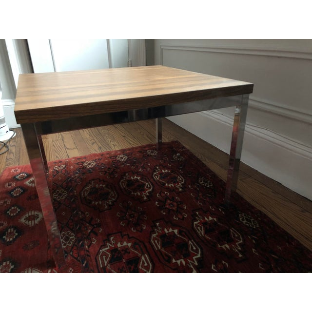 This is a great, well built little chrome plated steel and laminate side or coffee table. Top Is made of walnut color...